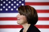 Senator Amy Klobuchar is pictured standing side on in front of a US flag.