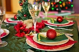 A dining table decorated with Christmas baubles, a tree and holiday-themed napkins.
