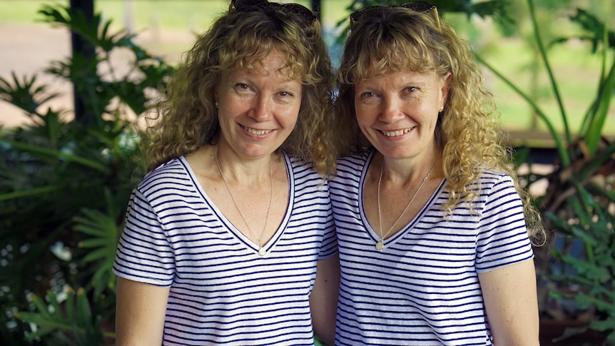 Identical twin sisters stand side-by-side smiling in identical outfits