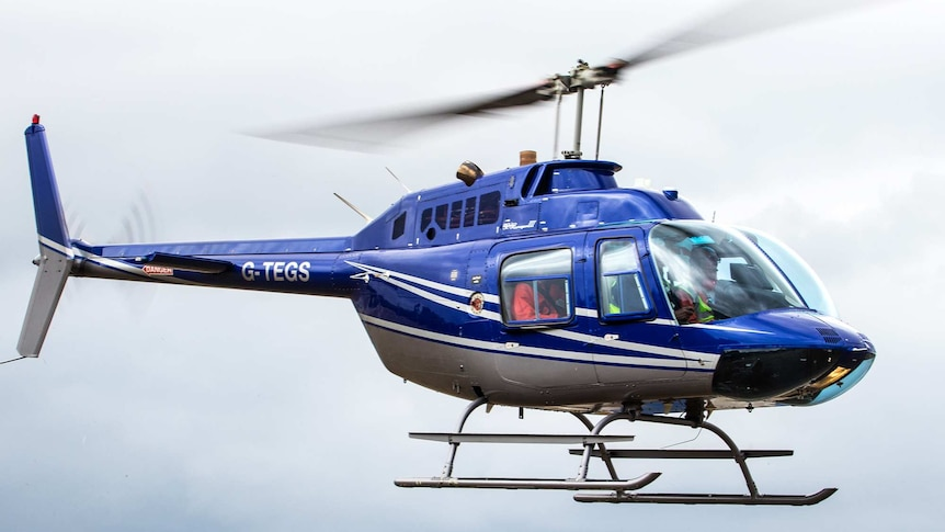 A blue helicopter flies in the air.