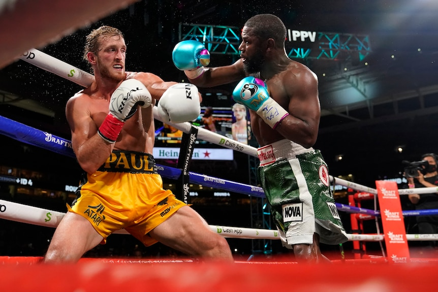 Logan P{aul backs away from Floyd Mayweather in a ring