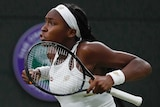Coco Gauff pumps her arms in celebration, racquet in hand.
