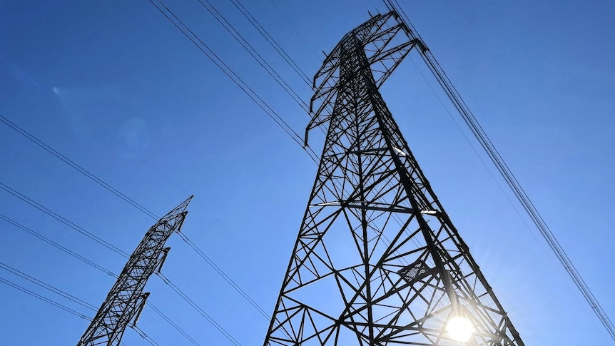 View directly up at two, high-voltage transmission poles shot from the ground up, blue sky in background
