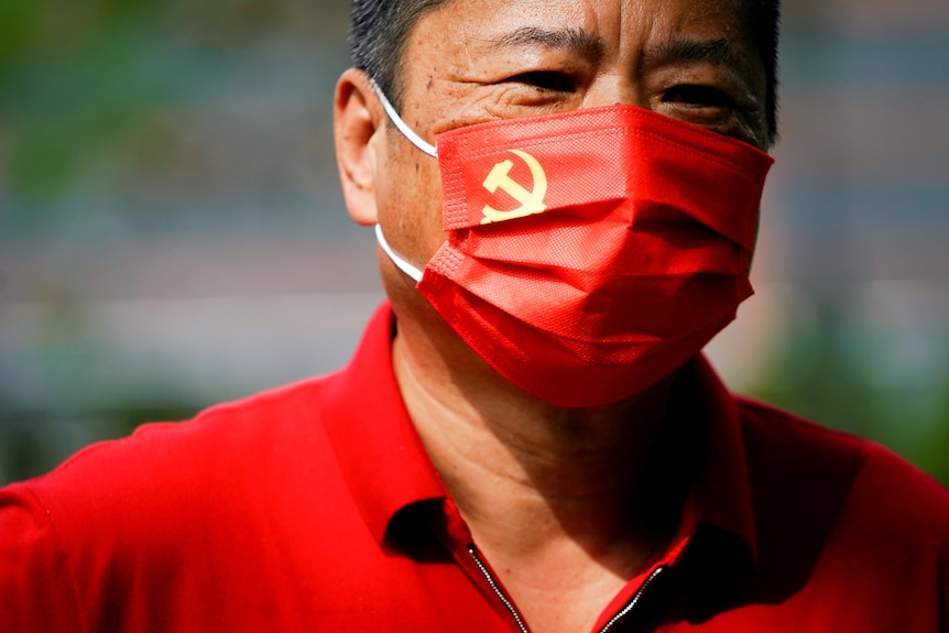 A man stares as he wears a red face mask with the CCP flag on the left hand corner.