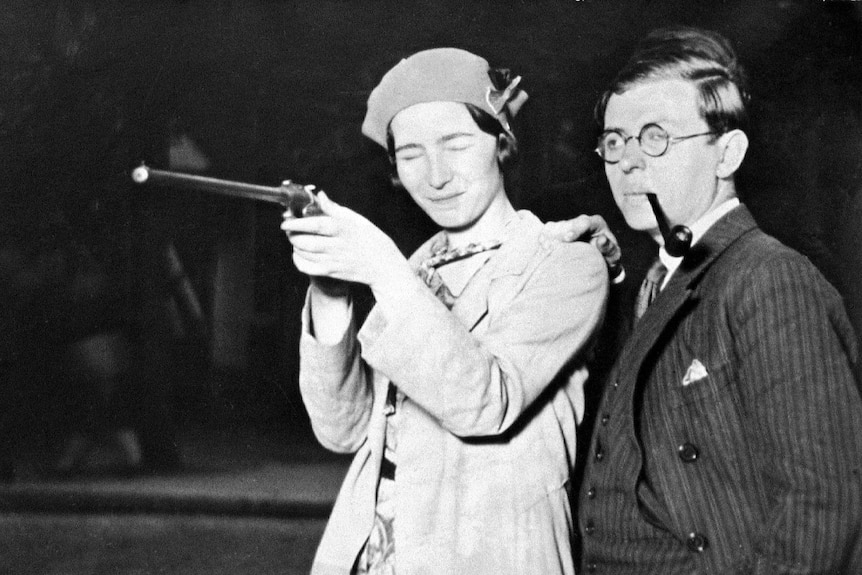 Simone de Beauvoir holding a gun, eyes closed, and Jean-Paul Sartre with pipe in mouth.