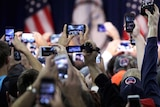 A sea of hands hold up their phone cameras as they wait for the arrival of Donald Trump.