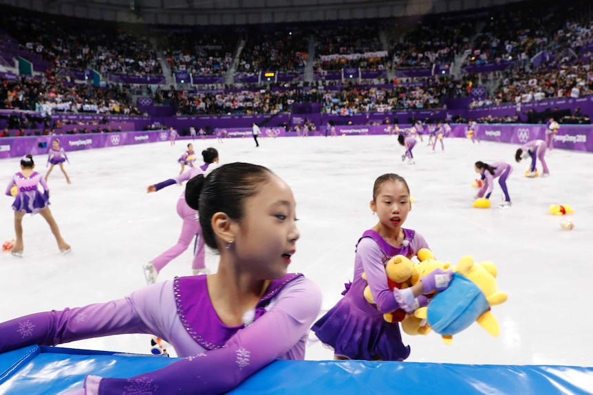 Skating girls collect Winnie the Pooh toys thrown on the ice during men's figure skating.