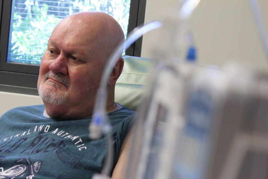 A middle-aged man receiving cancer treatment at a hospital