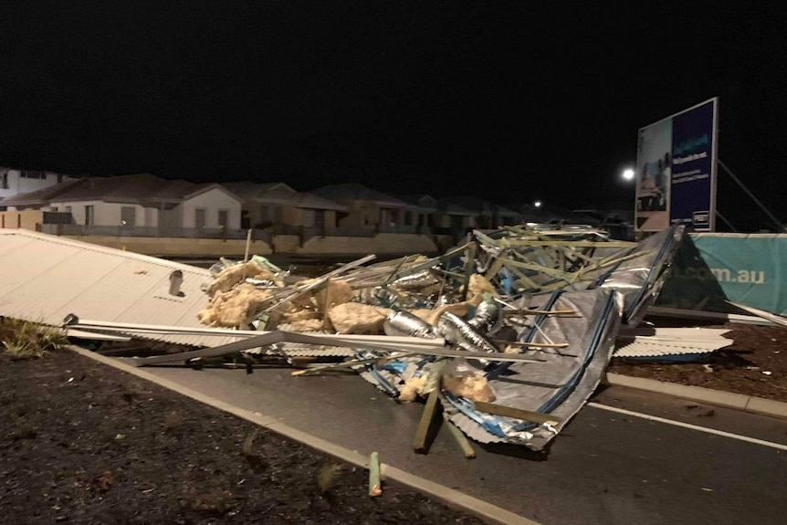 The mangled roof of a house lies on a road with houses in the background.