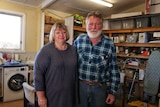 An older couple stand in what looks like a shed, their arms around each other. They look a bit beleaguered.
