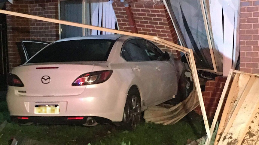A white car crashed into a red brick house, badly damaging it.
