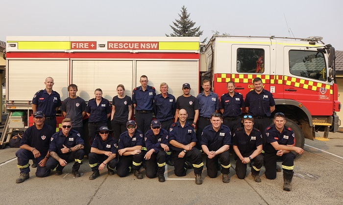 a fire truck behind a group of firefighters in blue uniforms