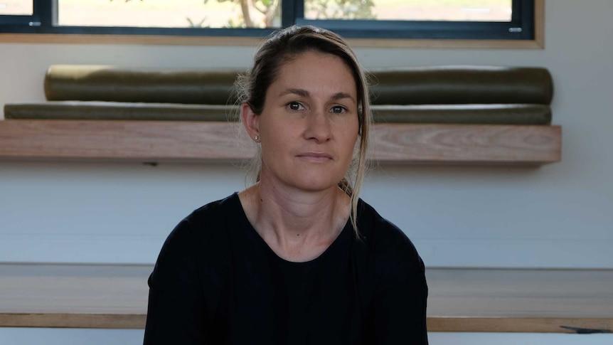 Jane Fleming sits on steps inside her house.