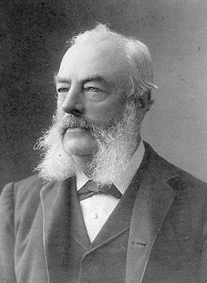 A black and white photo of a man with fluffy white muttonchops