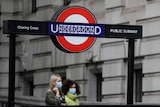Two women wearing facemasks walk under a sign for the London Underground