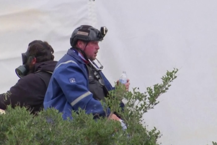 A man sitting down, wearing a blue jacket and a black helmet with a camera attached to the front holding a bottle of water.