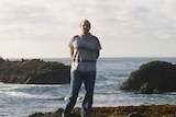 A man stands on a rocky shore.
