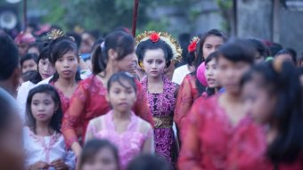 A group of Indonesian girls and young women stand in traditional attire.