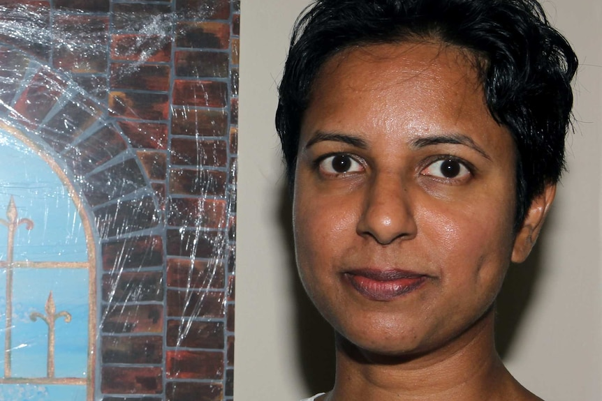 A tight head shot of Chamari Liyanage standing next to a painting.