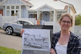 A woman holding a black and white drawing of a house, standing in front of the same real house.