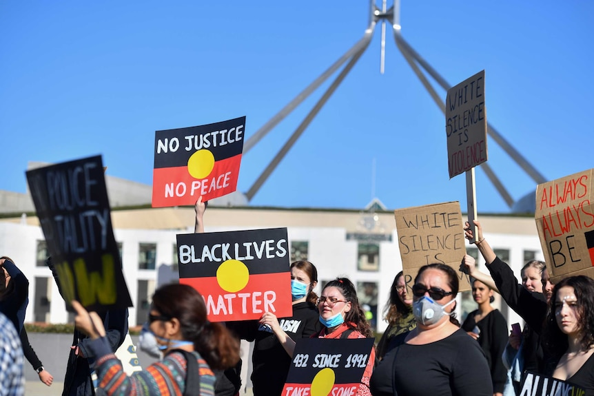 """People holding placards with the Aboriginal flag reading """"Black Lives Matter"""" march in front of Parliament House."""