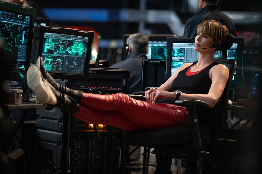 Charlize Theron leaning back in her chair with her feet up on a desk in Fast and Furious 9
