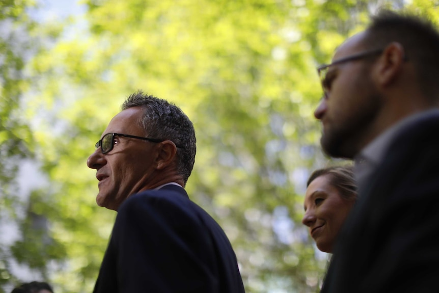 Adam Bandt and Larissa Waters stand behind Richard Di Natale in a courtyard at Parliament House