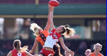 Female players reach for the football during an AFL game.