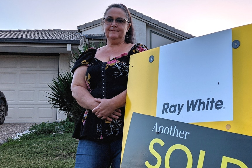 Kerri Rye standing by the sold sign outside her rental property
