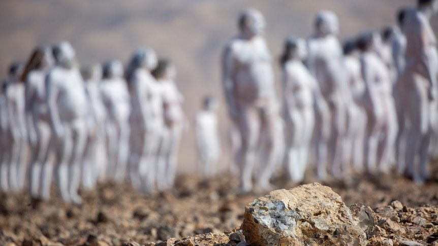 A rock sits in the foreground in the desert as naked people painted white stand, blurry, in the background.