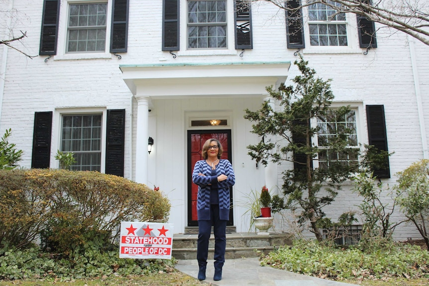 A woman in a blue chevron print cardigan standing outside a DC home with a 'statehood for people of DC' sign in the grass