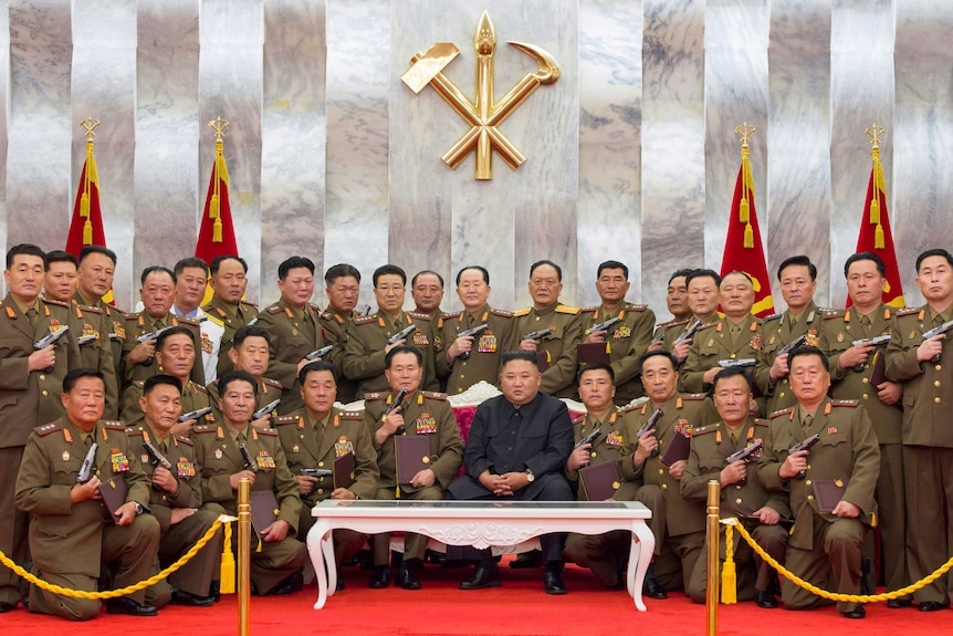 A photo of Kim Jong-un surrounded by soldiers brandishing hand guns