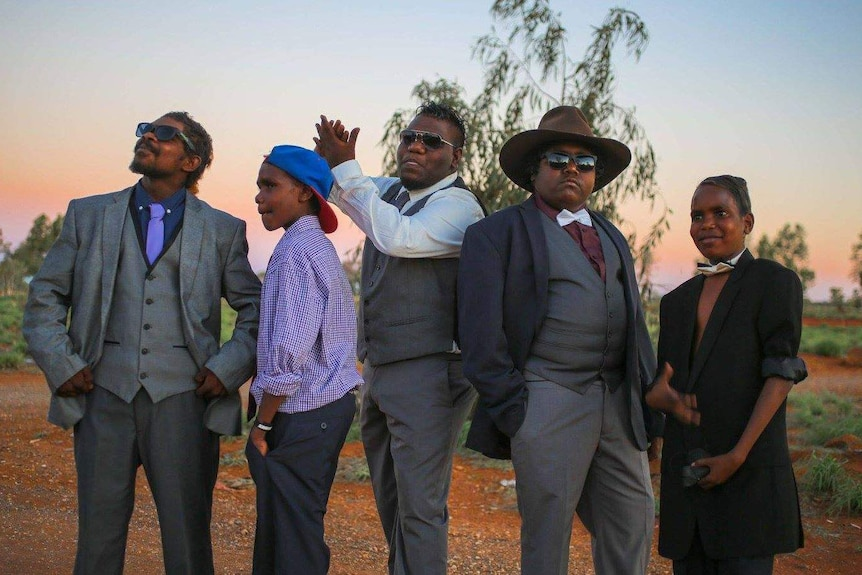 A group of male models pose at the 2017 Kiwirrkurra Fashion Show