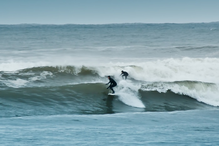 A couple of people riding waves on surfboards.