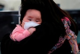 A child wears a mask to prevent an outbreak of a new coronavirus in Hong Kong.