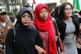 A woman in a red headcarf walks flanked by two other women and reporters and police on her way to court.