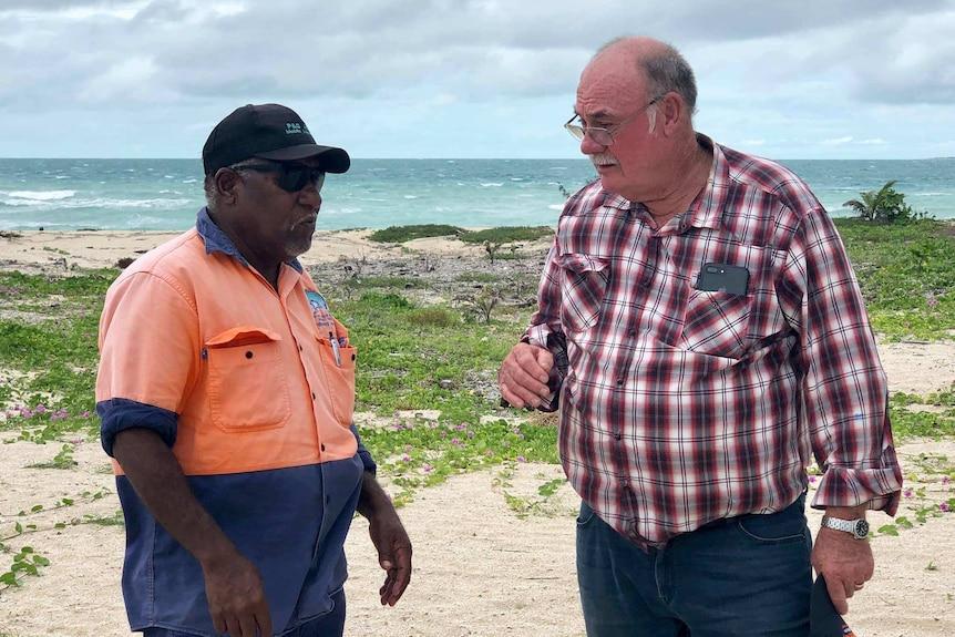 Warren Entsch talking to a Torres Strait Islander with the sea in the background.