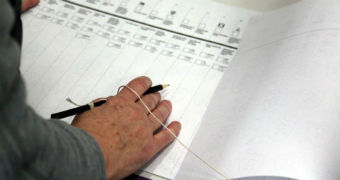 A voter holds a tethered pencil in their right had as they fill out a Senate ballot paper