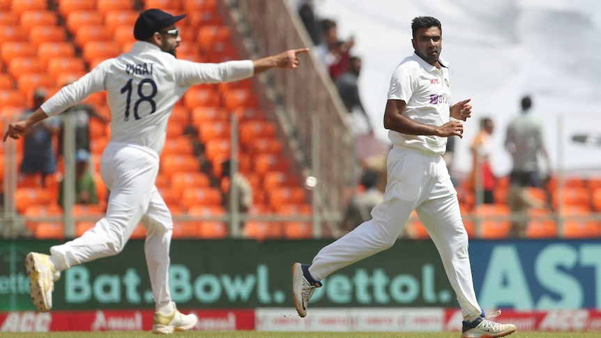 A cricket captain runs, pointing, in celebration of a wicket, as the bowler runs with him in a Test.
