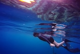 A photo of a snorkeller just below the surface of the sea