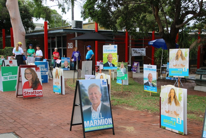 A group of volunteers wearing election campaign t-shirts stands outside a voting centre surrounded by election campaign posters.