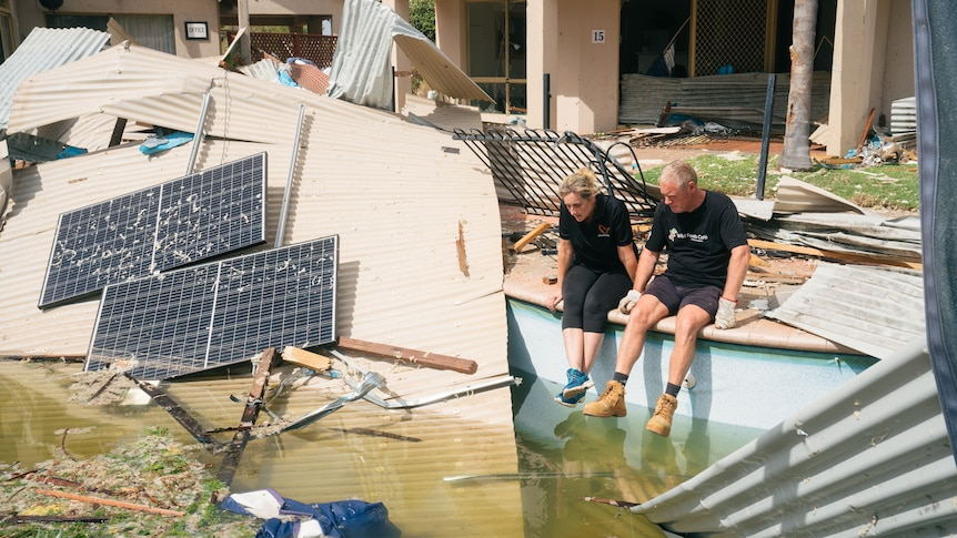 Two people sit on the edge of a pool with debris strewn all around them