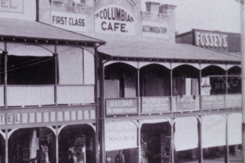 A black and white photo showing a line of shopfronts along a main street in the 1930s.