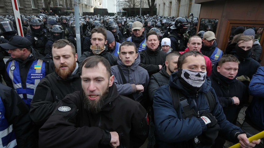 A group of men who are members of Ukraine's National Corps far-right activist group rally, with police behind them.