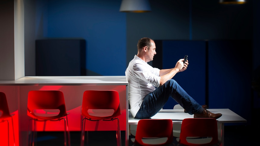 A man sits on a table using his mobile phone with chairs in the foreground.