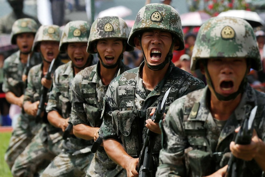 A group of Chinese soldiers shouting while grasping bayonets