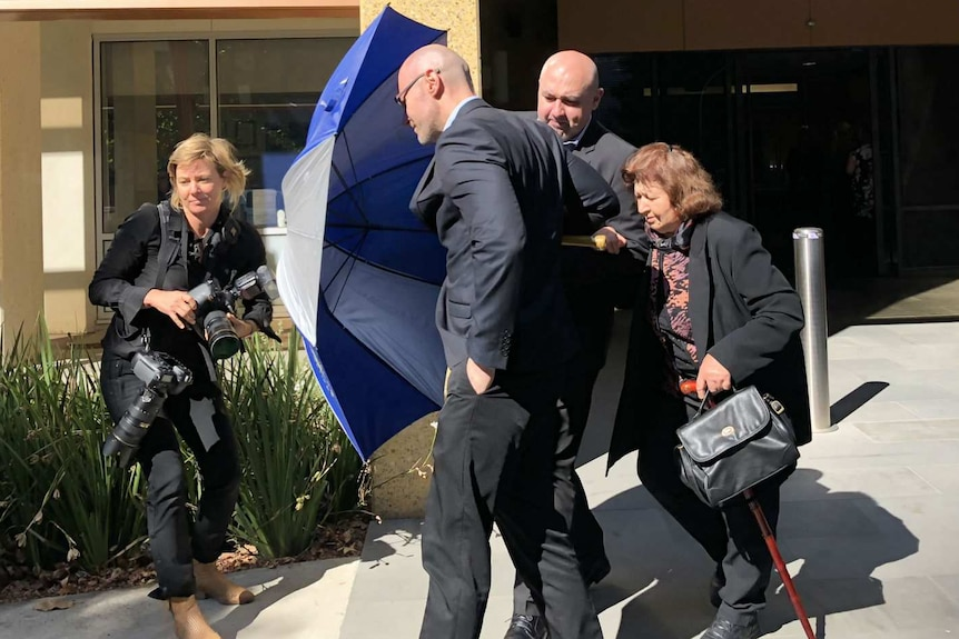 Dragi Stojanovski uses an umbrella to shield his brother and mother from a photographer as they leave the Coroners Court.