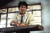 Jackie Chan holding a piece of wood, covered in sweat and cuts, in the film Police Story 2