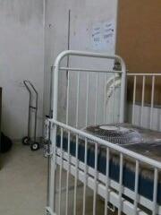 A dirty room with a hospital bed, which has a broken fan on it.