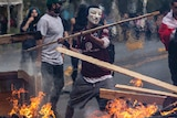 A masked protester throws a plank of wood into a burning barricade in Santiago